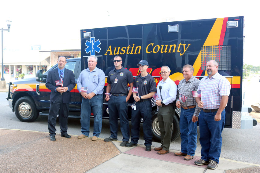 Pictured Monday morning in front of Austin County's new ambulance are, from the left, Judge Tim Lapham, Commissioner Mark Lamp, EMTs Sacha Masson and Bryce Armstrong, EMS Director Walter Morrow, and commissioners Bobby Rinn and Chip Reed. They are holding flags in honor of Flag Day last Friday.