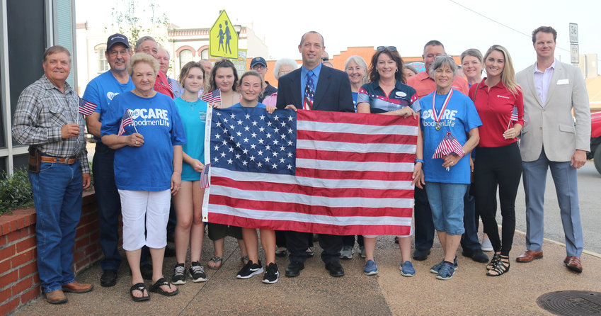 County Judge Tim Lapham, center, and Woodmen of the World representative Dorothy Dunsworth, to the right of Lapham, and other Woodmen of the World representatives and county officials pose Monday for a proclamation and flag presentation in recognition of Friday being Flag Day.