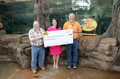 Andy Wohlgemuth, community and social media coordinator for Bass Pro Shops, Ali Dodson, advancement director for the Katy Prairie Conservancy, and JR Young, general manager of Bass Pro Shops, participate in a check presentation.