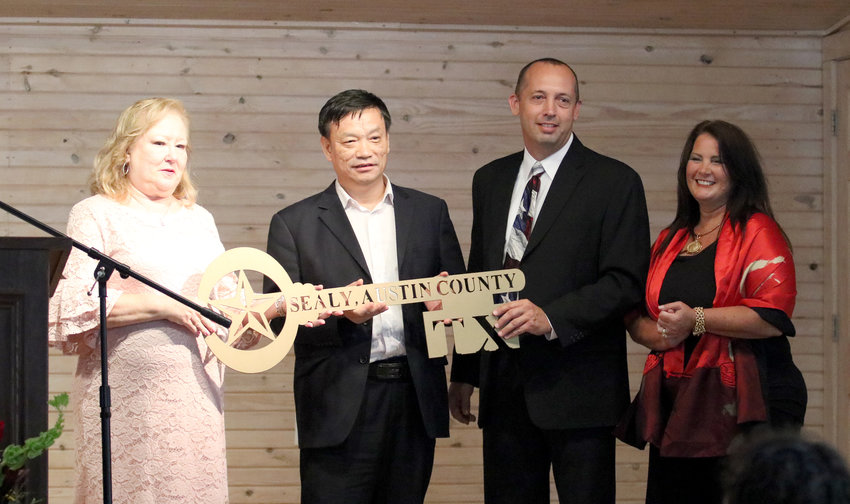 Local officials present a key to the city to Hailiang Copper Texas CEO Hu Wang, second from left, during a ceremony Tuesday at Liedertafel Hall. Making the presentation are Sealy mayor Pro-tem Sandra Vrablec, County Judge Tim Lapham, and Lapham's Senior Executive Assistant Dianna Grobe.