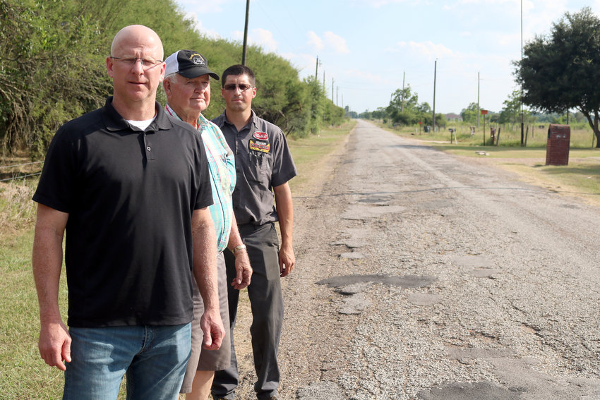 Darren Brandes, James Schroeder, and Ross Carpenter stand alongside Grubbs Road north of Sealy. The residents said they are tired of the deteriorated condition of the road and what they say is a lack of response from the county to fix it.