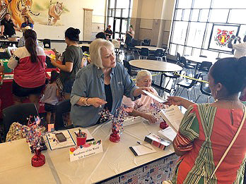 Patricia Knapp (standing) and Gladys Frank (seated) of Woodmen Life participate in the Back to School Health Fair held recently in Sealy.