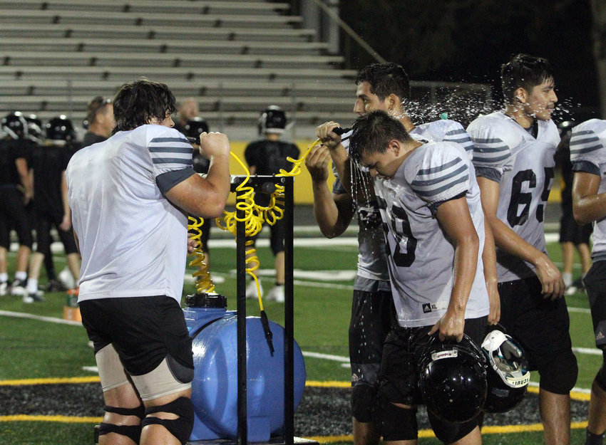 Sophomore Jose Arriaga uses the water cow to cool himself off during last Friday's Midnight Madness football practice at Sealy High School.