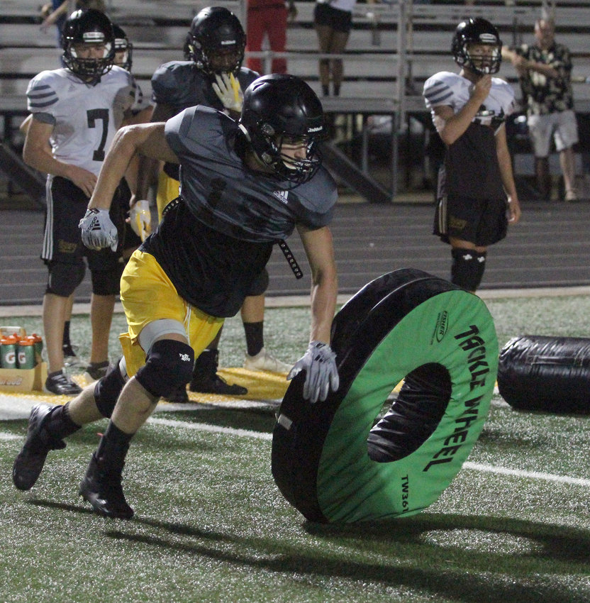 Cody Manna shucks one tackling wheel in anticipation of another one during Midnight Madness practice at the end of last week. The first practice where pads could be worn, the Tigers got on the field as the clock struck midnight, serving as their sixth day of workouts, making them eligible to start contact.