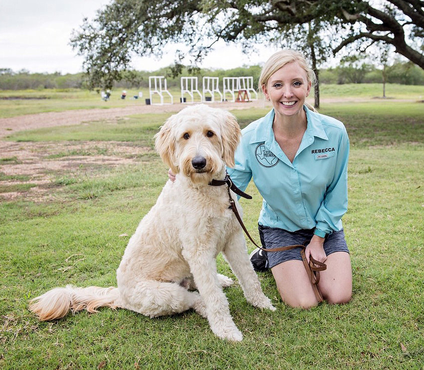 Rebecca Morone of Texas Premier Sporting Arms poses with her dog Charlie at the shooting range south of Sealy.