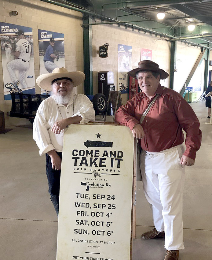 Tony Tristan and Joe Southern pose by a Sugar Land Skeeters playoff sign dressed in Texas Revolution outfits.