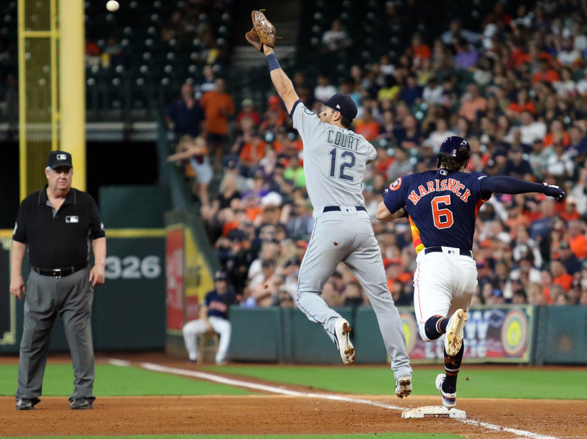 Jake Marisnick of the Houston Astros races the throw to first baseman Ryan Court of the Seattle Mariners during Sunday's game in Minute Maid Park. The Astros won, 21-1.