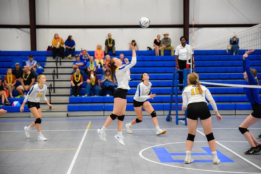 Regan Woodley returns the ball while Tyler Johnston, Addie Keuspert and Gabriella Yates await the next hit.