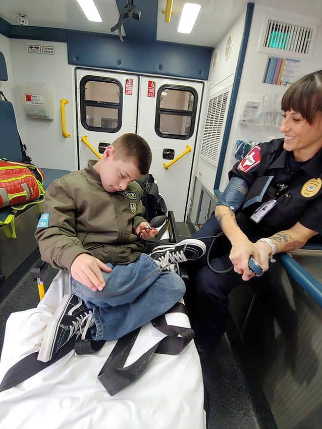 Melissa Thompson, a paramedic at Simonton/Fulshear who lives in Sealy, shows Christopher Schulte, son of Misty Schulte, how to take blood pressure readings during a tour of the fire station.