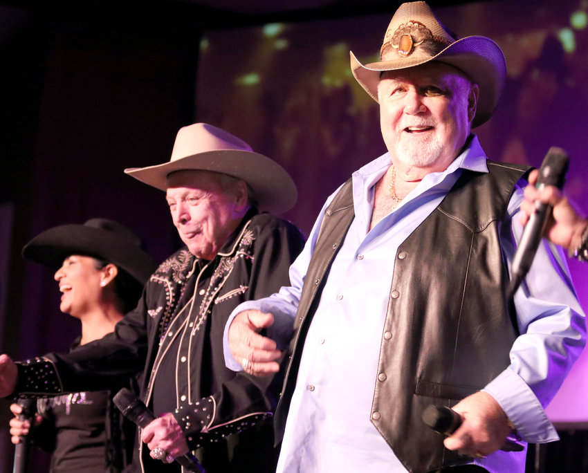 """Mickey Gilley, left, and Johnny Lee perform hit songs from """"Urban Cowboy"""" during their concert Friday night at the Austin County Fair."""