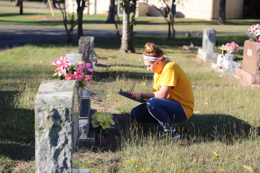 Sealy High School Student Council President Maddie Goad marks graves of veterans at the Sealy Cemetery before last year's Wreaths Across America event.