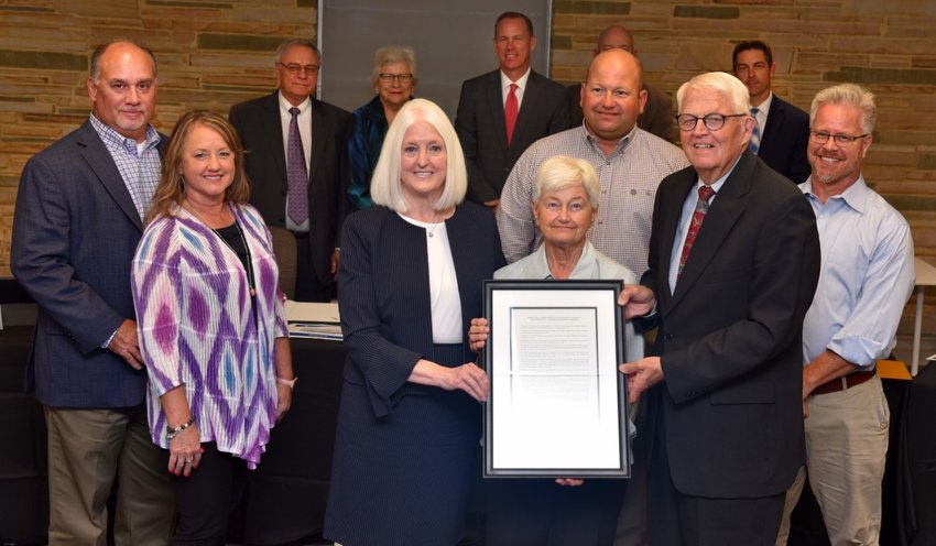 Holding the resolution are Dr. Mary Hensley, Chancellor of the Blinn College District; Barbara Powell; and Charles Moser, Chair of the Blinn College District Board of Trustees. Behind them, family members from left are Tommy and Debra Billeaud, Chip Powell, and Doug Peck. In the back row, from left, are Trustees Douglas Borchardt, Teddy Boehm, Jim Kolkhorst, Dennis Crowson, and Jason Jennings.