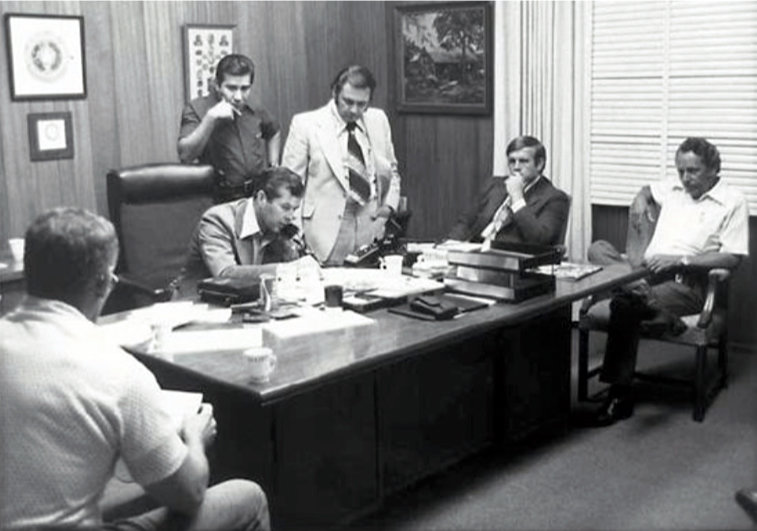 """TDC Director W.J. Estelle Jr. negotiates on the telephone, surrounded by other members of the """"Think Tank"""" who worked to manage the crisis inside the library. From the left are FBI agent Robert Wiatt, TDC interpreter Ben Aguilar, Carrasco's attorney Ruben Montemayor, public information officer Ron Taylor and Captain G. W. Burks of the Texas Rangers. (TDCJ photo)"""