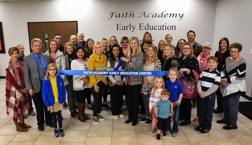 Faith Academy faculty joined Early Education Department Director, Tammy Shuck (with scissors), and Sealy Chamber of Commerce representatives for the ribbon-cutting ceremony that officially opened the new building.