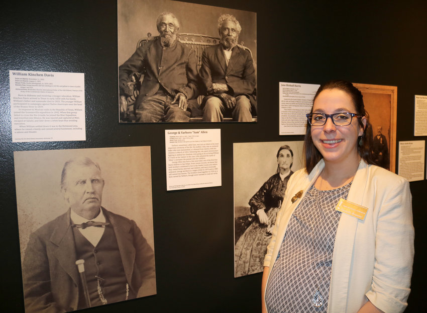 """Danielle Brissette, curator of the """"Faces of Austin's Colony"""" exhibit at the San Felipe de Austin State Historic Site and Museum, shows some of the 65 portraits on display depicting original inhabitants of San Felipe."""