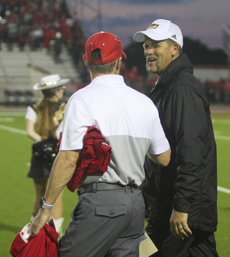 Coaches Grady Rowe, left, of Bellville, and Shane Mobley, right, of Sealy, could have their teams playing in the same district once again for the next two years through UIL realignment. The final district realignments won't come until February. Pictured is a pre-game meeting before this year's game on Sept. 20, at the Pasture of Pain where the Tigers came out of Bellville with a 34-14 victory.