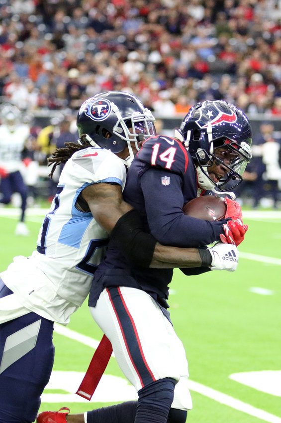 Houston Texans receiver DeAndre Carter (14) is tackled by a Tennessee Titans defender during Sunday's game at NRG Stadium. The Titans beat the Texans 35-14.