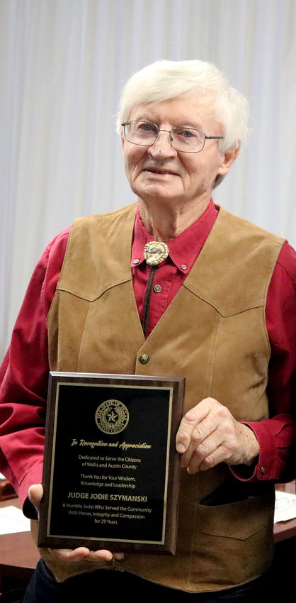 Wallis Municipal Judge Jodie Szymanski was presented a plaque by Austin County thanking him for 29 years of service to Austin County and the City of Wallis during the Jan. 13 meeting of Austin County Commissioners Court.
