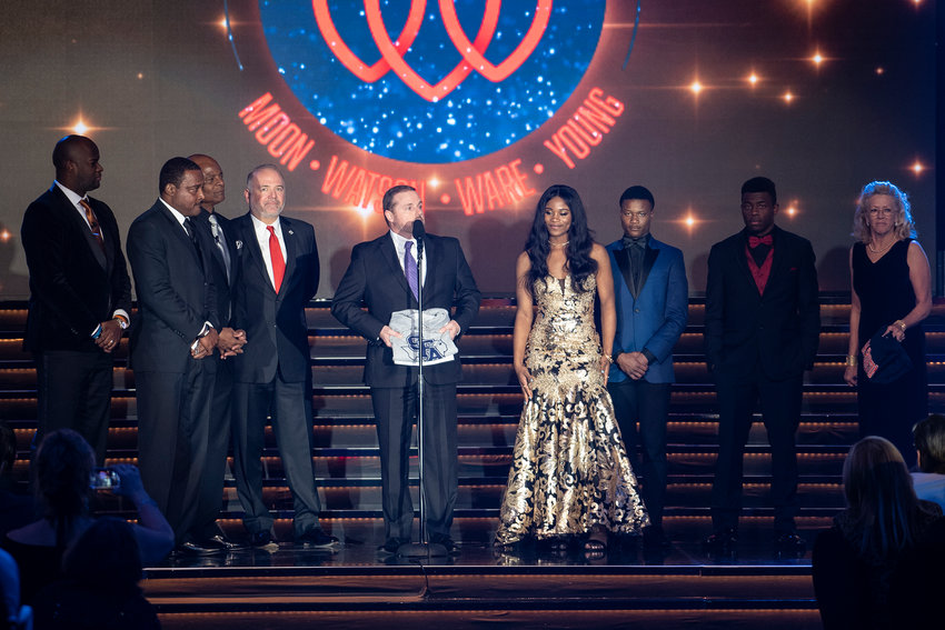 "Sealy High's Matthew Lord (second from right) was honored on the stage of last Monday's Houston Sports Awards ceremony at the Hilton Americas - Houston as one of three Brothers in Arms scholarship winners. It was on the stage that he, along with fellow winners Langston Ellis (next to Lord) and Vankey ""Blu"" Burks, learned of their acceptance into the universities of their choice, as explained by Stephen F. Austin University President, Dr. Scott Gordon (at microphone). On the far left are quarterbacks Vince Young, Andre Ware and Warren Moon who created the Brothers in Arms Foundation."