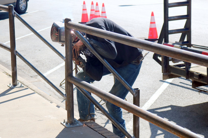 John Peck of Double M Fencing welds together railings that are going up along sidewalks downtown to help improve safety.