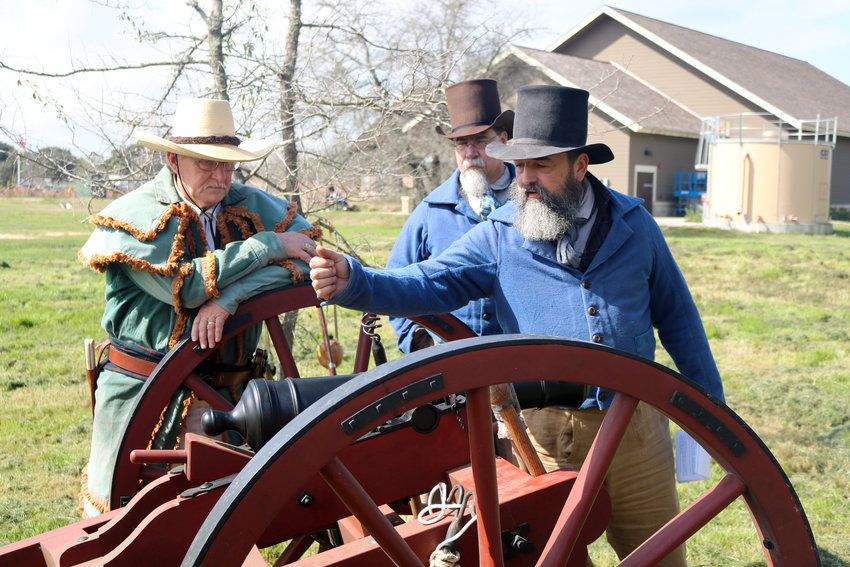 Clark McKinley of Bellville and Mike Covington watch as Frank Marek demonstrates cannon safety during the Militia Muster Saturday at San Felipe de Austin State Historic Site. The muster was a call to volunteers to come and learn how program areas will work once the Villa de Austin, a replica village of the original San Felipe, is built.