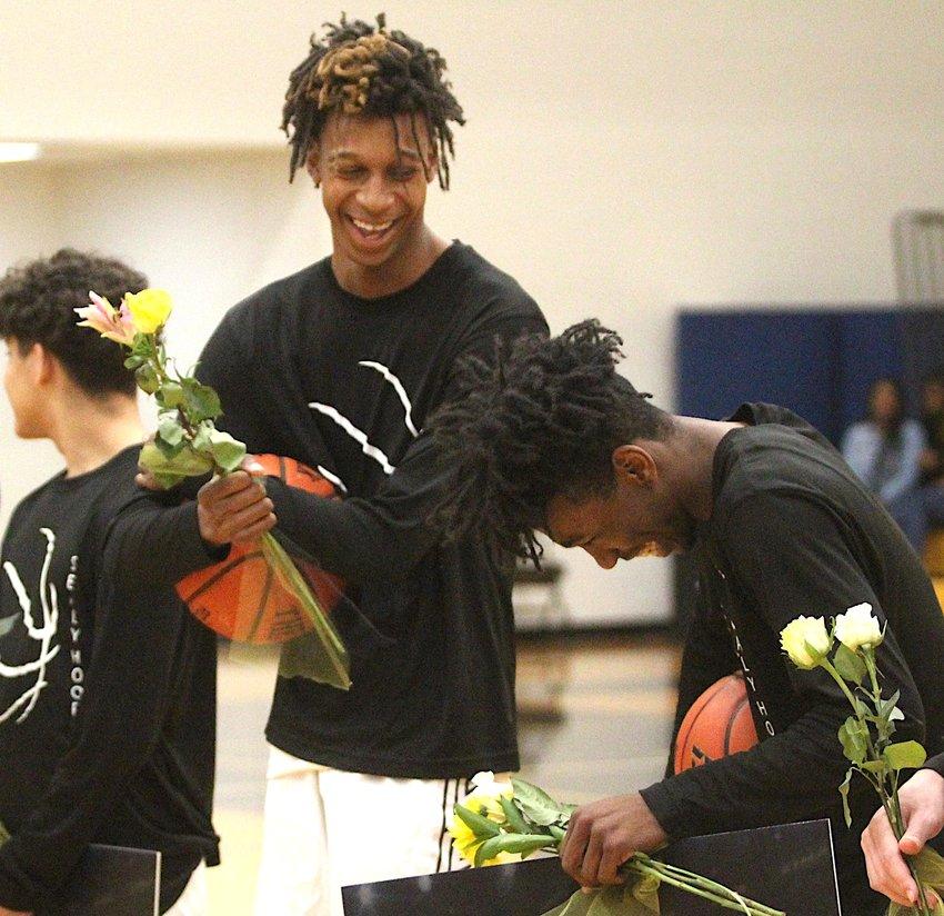 Seniors Donte Beasley (left) and Ja'Marris Cotton (right) share a laugh during the pregame ceremony that honored all the Tiger seniors before their final basketball game last Tuesday at Sealy High School against the Royal Falcons.