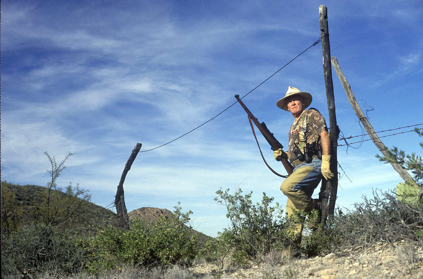 An intrepid hunter leans against a weathered gate post, the tallest structure available in the arid Big Bend country of West Texas.