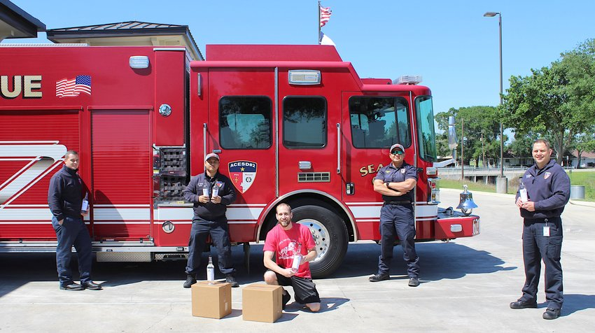 Shire Distilling Co. has transitioned all operations from producing whiskey and vodka to hand sanitizer to help mitigate the spread of COVID-19. Tim Raines (front and center), co-founder and master distiller, dropped off a box to the Sealy Fire Department last week. Pictured in back, from the left, are Steve Noack, Dio Valdez, Jeramie Casiano and Mark Karonika.