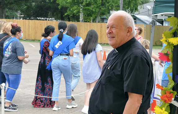 The Rev. Eric Pitre watches as a surprise parade in honor of his retirement goes by outside Immaculate Conception Catholic Church Sunday afternoon. Earlier he presided over his final Mass at the church.