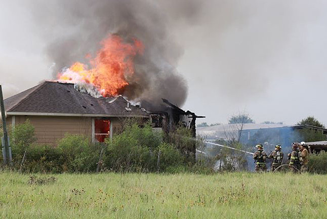 Firefighters battle a housefire Tuesday afternoon on Klopesteck Road.