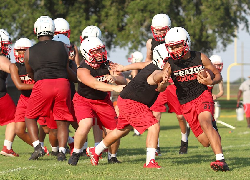 The Brazos Cougars hit the gridiron for the first official practice of the season Monday evening and also debuted the new white helmets they will be wearing this year. Pictured is Vincent Aguilar carrying the ball during a drill Monday evening at Brazos High School.