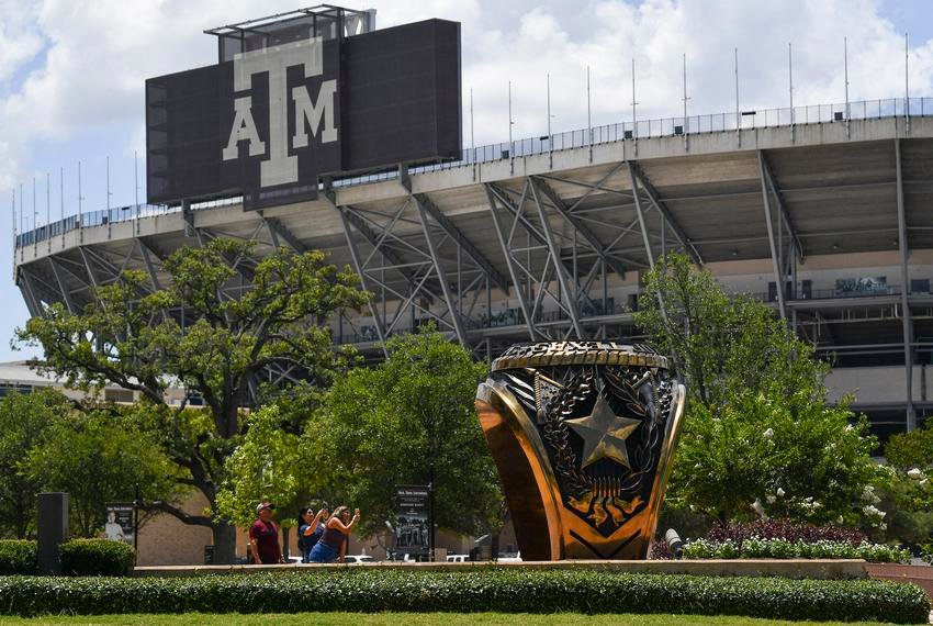 People take photos with the 3-ton bronze replica of the Haynes Aggie Ring at Texas A&M University on Monday, June 15, 2020 in College Station. The ring is located outside the Clayton W. Williams Jr. Alumni Center near Kyle Field.