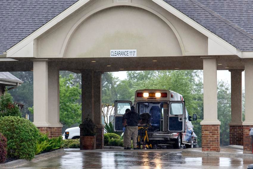 Paramedics disinfect a gurney in their ambulance before leaving a nursing home in Tomball. This week, in Missouri County, locals expressed concern over 17 deaths that occurred from an outbreak at a nursing home.