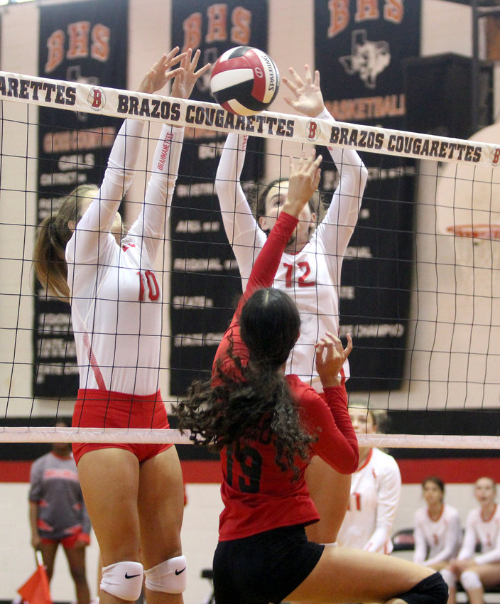A pair of Brahmanettes go up for the block in the first set of an in-county, non-district volleyball game between Brazos and Bellville in Wallis last year.