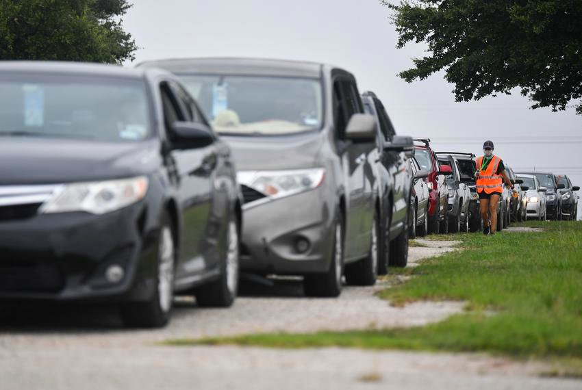 Cars lined up for a drive-thru food distribution hosted in June by the Central Texas Food Bank in Austin. More than 1.7 million Texans are receiving unemployment benefits, and nearly 350,000 don't qualify for an additional $300 each week in federal aid.