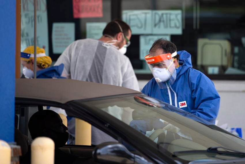 A health care worker speaks to a patient at a drive-thru coronavirus testing site in Garland.
