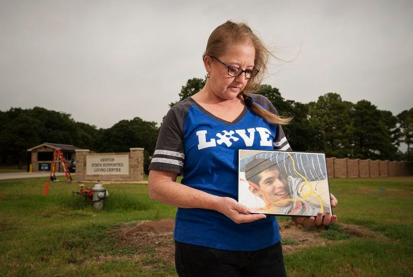 Stephanie Kirby holds a photo of her son Petre Kirby outside of the Denton State Supported Living Center, where her son is a resident. She hasn't seen him since March because of COVID-19.