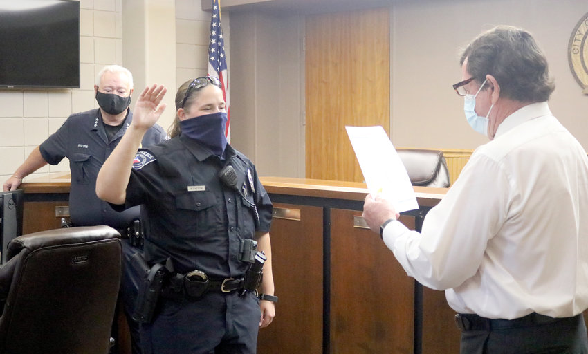 Karissa Nickeson is sworn in as a new patrol officer for the Sealy Police Department by Sealy City Manager Lloyd Merrell (right) Monday morning at City Hall. Behind Nickeson is Sealy Police Chief Jay Reeves.