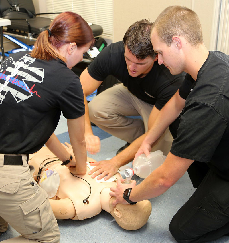 Blinn Emergency Medical Technician Program students practice on a dummy.