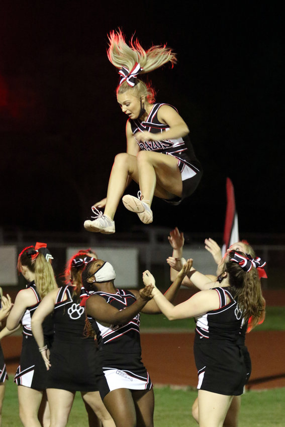 Brazos High School cheerleader Madi Kneip falls into the arms of fellow cheerleaders Emma Tidwell, left, and Aubani Cormier during halftime of Friday's football game with East Bernard. The Cougars fell to East Bernard 62-6.