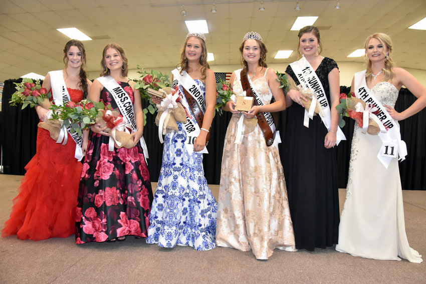 Ashlin Gordon, third from right, of Bellville was crowned queen of the 93rd annual Austin County Fair Saturday night. Rileigh Dinges, who sold $16,620 worth of tickets, was named ticket queen and was second runner-up. Pictured from the left are first runner-up ticket queen Emma Grace Fogle, Miss Congeniality and third runner-up Emily Lewis, Dinges, Gordon, first runner-up Avery Oliver, and fourth runner-up Maddie Kneip. Presenting the sash to Gordon is last year's queen Emma Lischka.