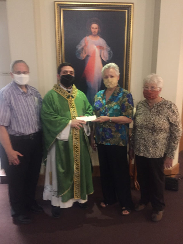 KJT Society No. 80 President Barbara Hajdik presents a matching grant fund check to Father Jonathan More of Immaculate Conception Church. Looking on are society Treasurer Steven Kutra and Secretary Bernice Stolarski. Society No. 80 sponsored one of the drive-thru food lines at the recent church bazaar in order to qualify for the funds.