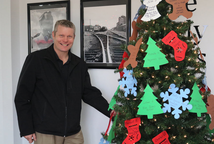 Russ Rainwater takes the first ornament off the Angel Tree last year. The Angel Tree benefiting the seniors at The Oaks and Silver Lakes retirement communities will go up Thanksgiving week at The Sealy News and be available on Friday, Nov. 27.