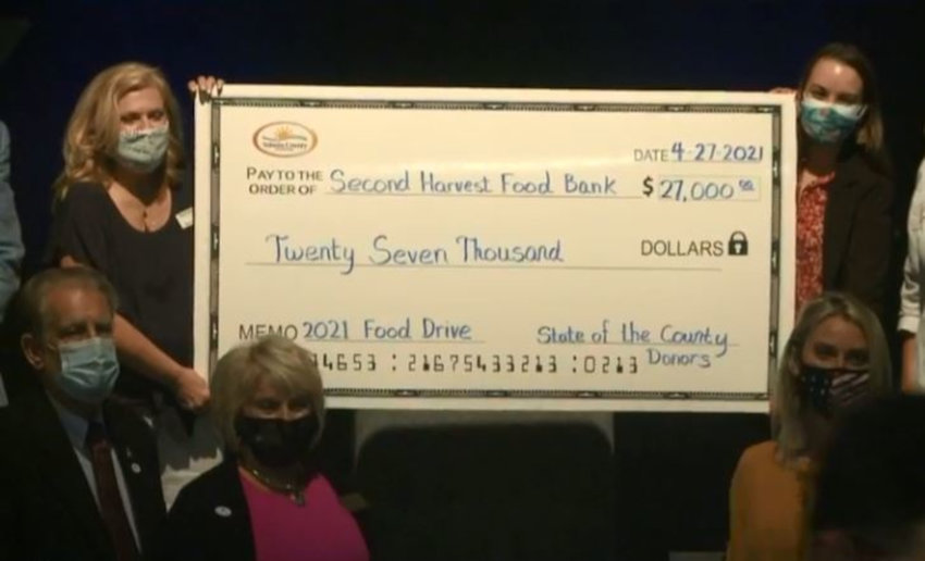 Representatives from Second Harvest Food Bank stand with members of the Volusia County Council as a $27,000 check is presented to the non-profit organization