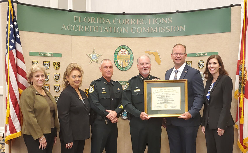 Court and Detention Services Chief Dan Engert (Left-middle) and Flagler Sheriff Rick Staly (Right-middle) accepting the accreditation from FCAC commissioners