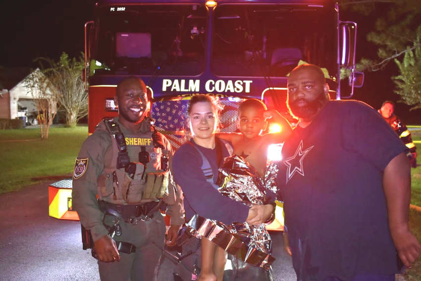 DFC Dawson with Palm Coast Fire Department, the toddler, and his father.