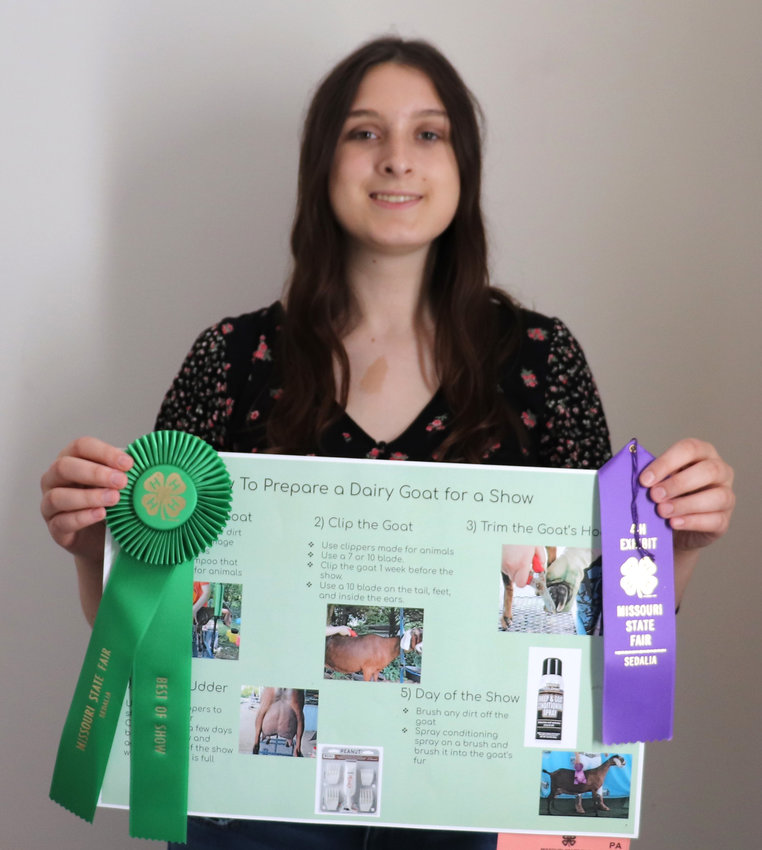 """Riley Edmunds poses for a photo with her """"How to Prepare a Dairy Goat For Show"""" Poster."""