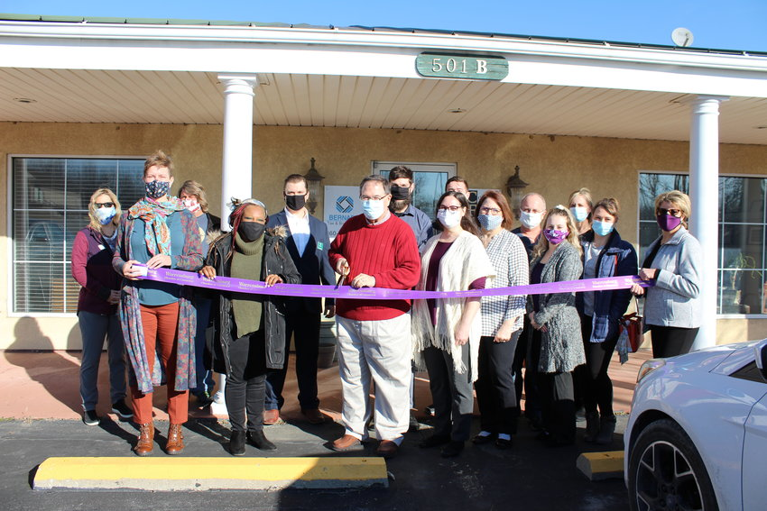 William Bernard cuts the ceremonial ribbon alongside Bernard Tax and Bookkeeping and Central Financial Services employees and Warrensburg Chamber of Commerce members Tuesday, Jan. 12.