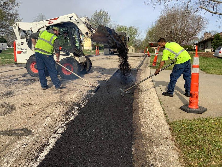 Street Department crew members Brad Butler, left, and Rick Love, right, work to repair a street in Warrensburg.