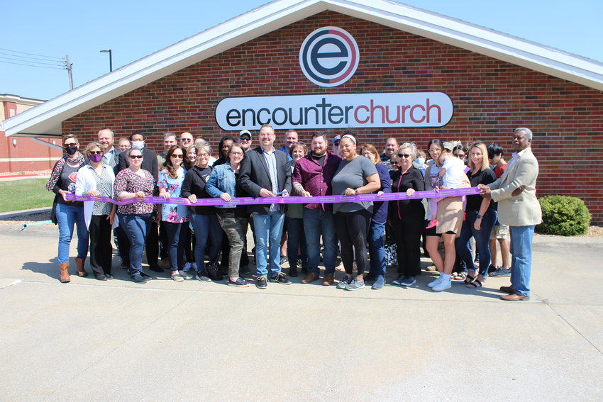 Encounter Church Lead Pastor Chris Gray prepares to cut the ceremonial ribbon alongside campus pastors Matt and Ashli Morgan, church members and staff and Chamber of Commerce members and staff.